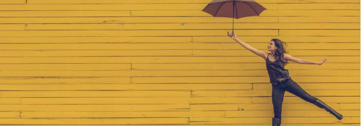 A woman holding an umbrella stands in front of a yellow wood slat wall. She is holding her right arm out with the umbrella open and left leg up off the ground.
